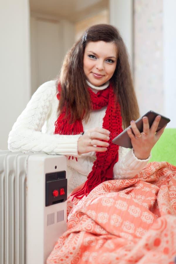 Женщина читает eBook около теплого радиатора стоковое изображение rf