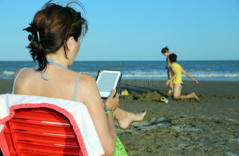 Женщина читает ebook пока ее дети играя на пляже стоковые фото