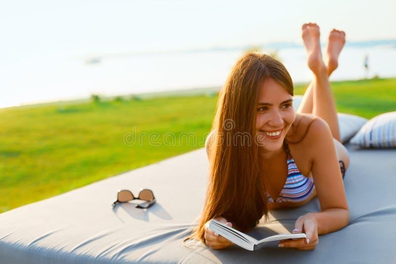 Женщина читая книгу на пляже стоковые изображения