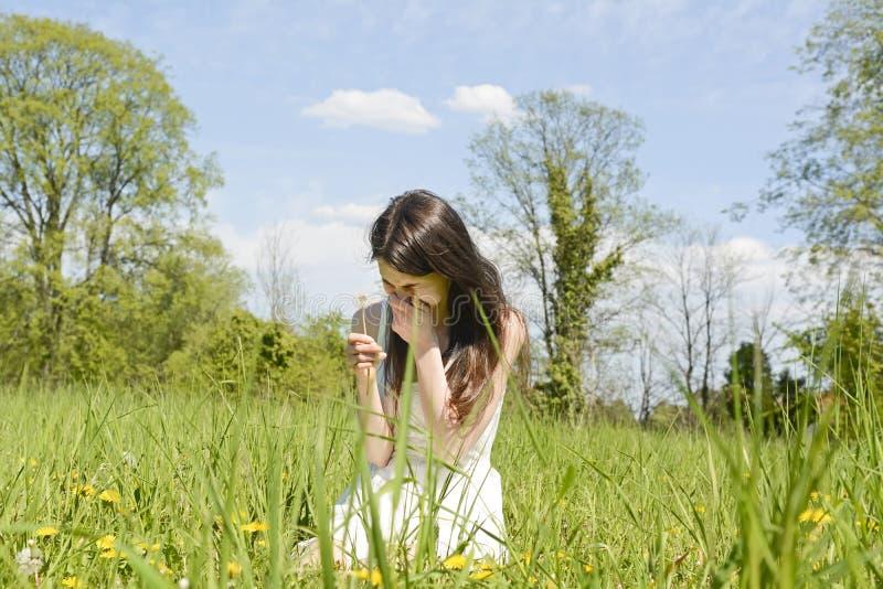 Женщина чихает на луге стоковое изображение