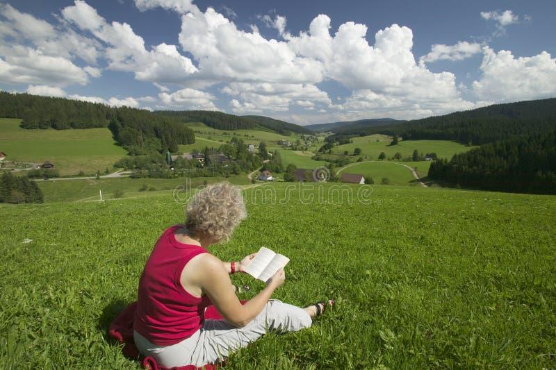 женщина чтения лужка стоковое изображение rf