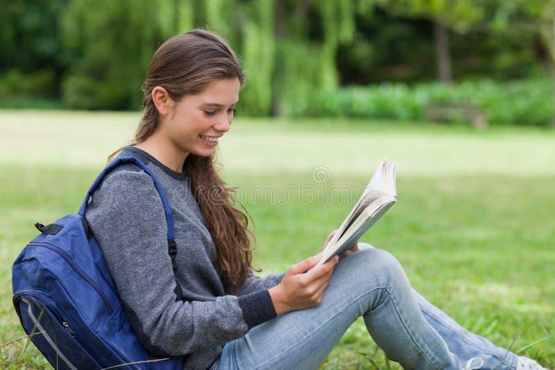 женщина чтения травы книги сидя стоковое фото rf