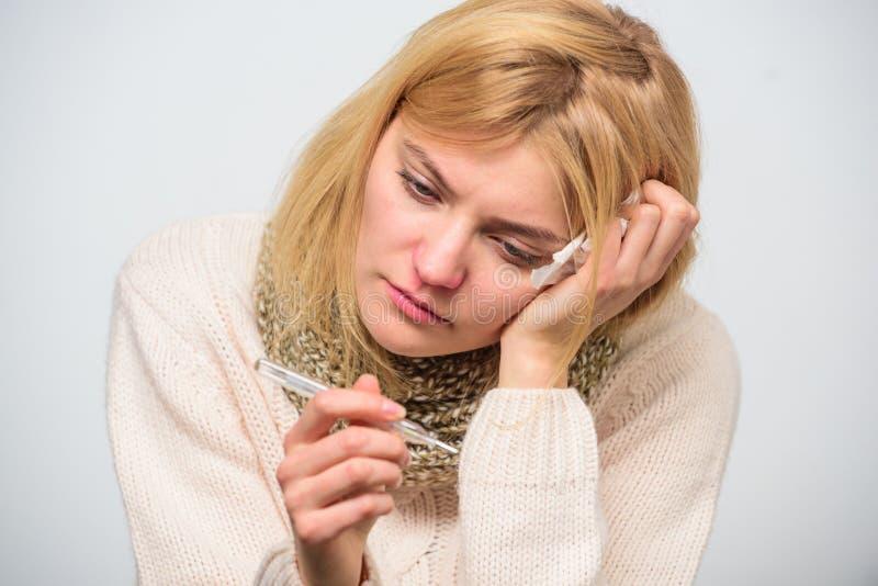 Женщина чувствует плохо больной чихать Девушка в поднимающем вверх термометра и ткани владением шарфа близкое Температура измерен стоковая фотография