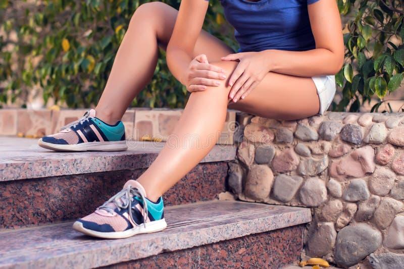 Женщина чувствует сильную боль колена пока делающ тренировки Концепция людей, здравоохранения и медицины стоковая фотография rf