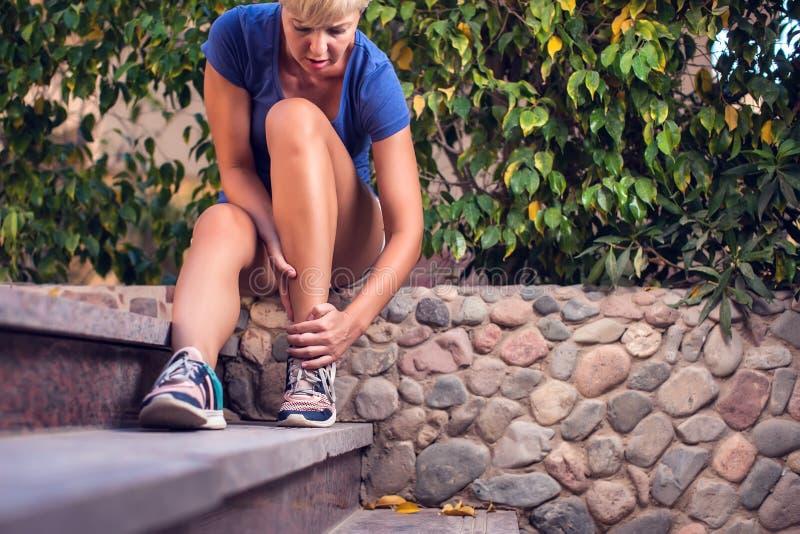 Женщина чувствует сильную боль ноги Концепция людей, здравоохранения и медицины стоковые фото