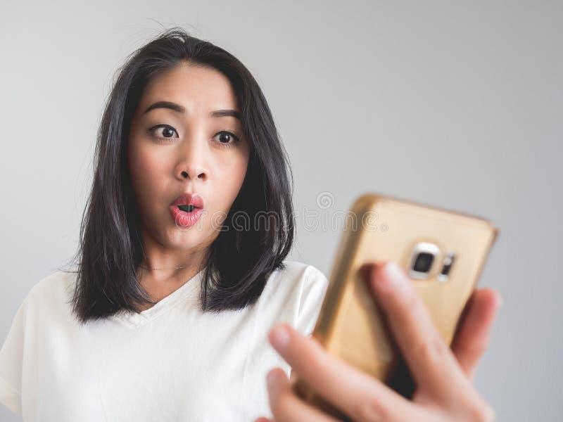 Женщина чувствует surpriesed на ее дисплее smartphone стоковое изображение rf