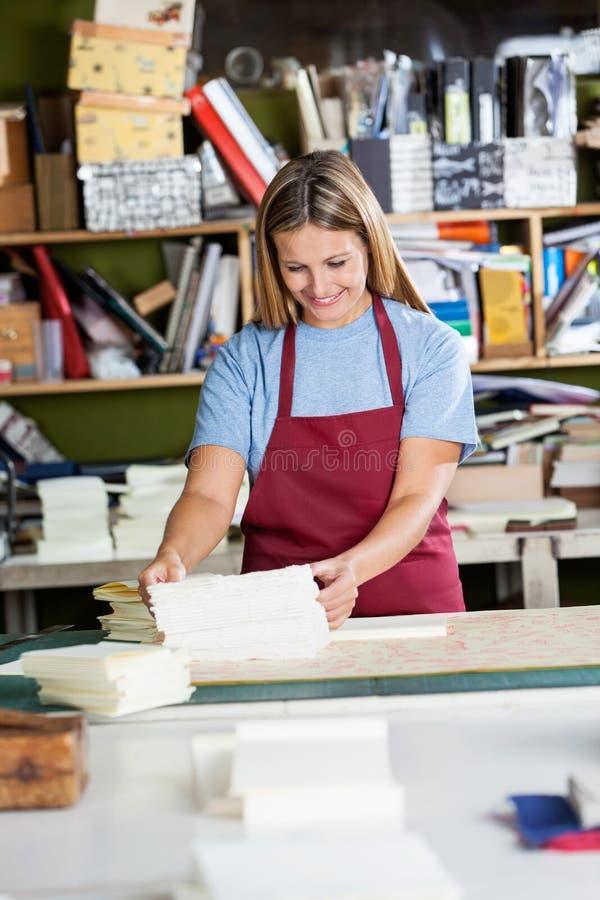Женщина штабелируя бумаги на таблице в фабрике стоковые изображения