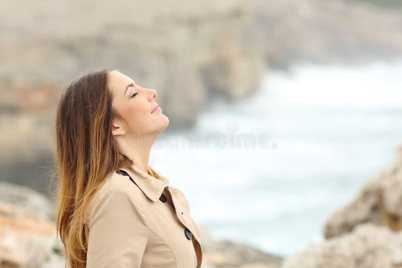 Женщина дышая свежим воздухом в зиме на пляже стоковое фото rf