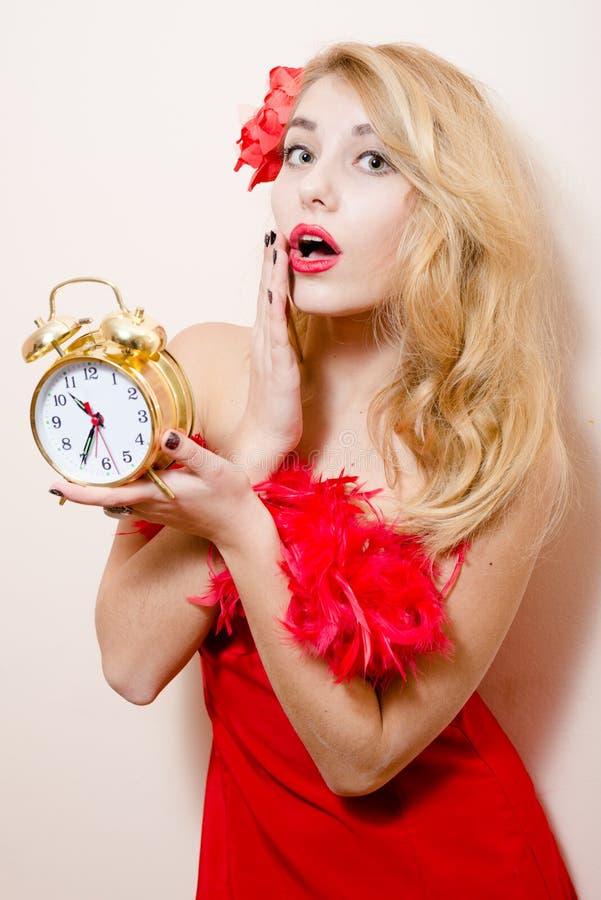Женщина agitated красивого смешного молодого белокурого pinup милая с будильником в красном платье wonderingly смотря камеру стоковые изображения