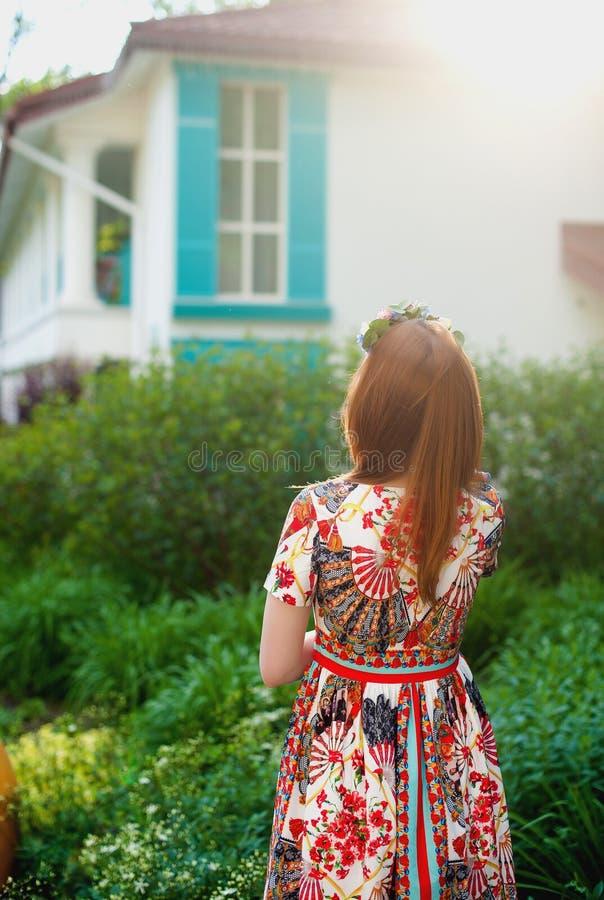 Женщина BBeautiful молодая рыжеволосая в ярком платье стоя в природе, смотря окна стоковые фотографии rf