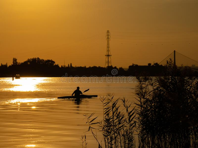 Женщина canoeing на заходе солнца на Реке Висла, Польше Изумительные пейзаж и цвета стоковые фото