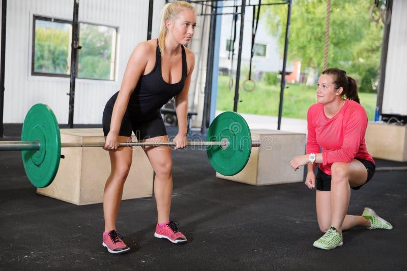 Женщина Crossfit поднимает весы с личным тренером стоковое фото rf