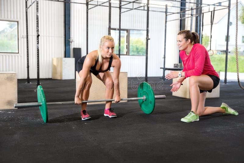Женщина Crossfit поднимает весы с личным тренером стоковое изображение rf