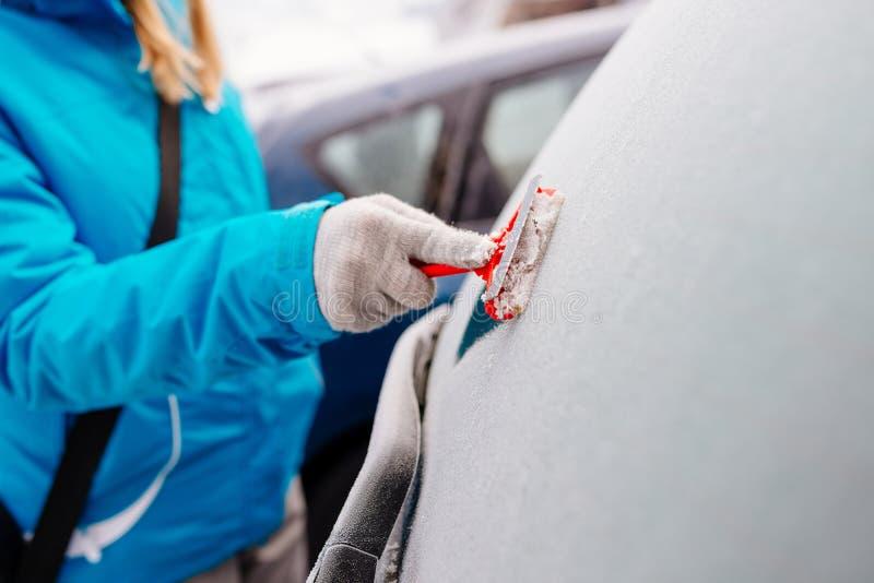 Женщина deicing заднее лобовое стекло автомобиля стоковые фотографии rf