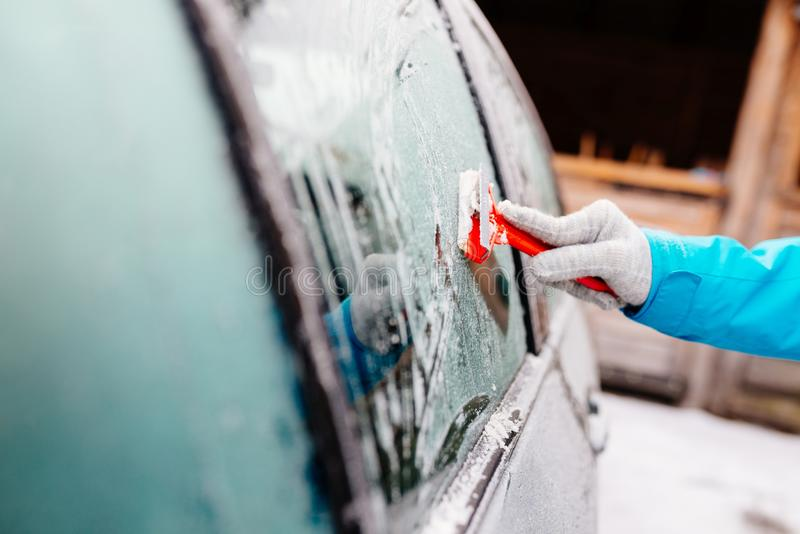 Женщина deicing лобовое стекло бортового автомобиля с шабером стоковые изображения rf