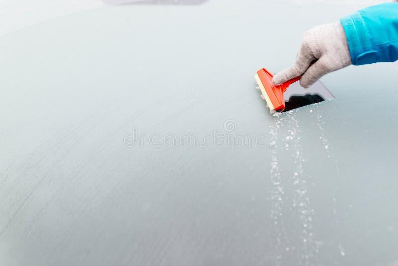 Женщина deicing переднее лобовое стекло автомобиля с шабером стоковые фото