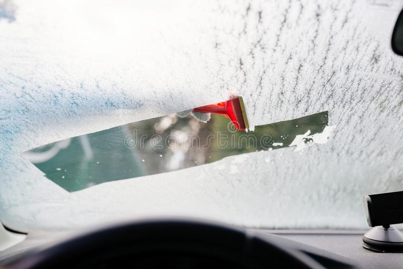 Женщина deicing переднее лобовое стекло автомобиля с шабером стоковая фотография rf