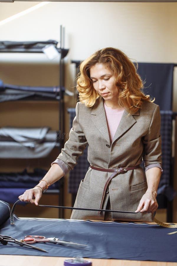 Женщина Dressmaker работая с измеряя лентой в atelier стоковые фото