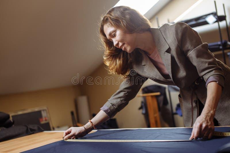 Женщина Dressmaker работая с измеряя лентой в atelier стоковые изображения