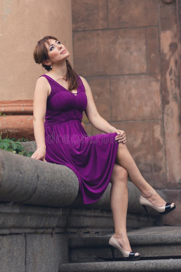 Женщина Eautiful в фиолетовом платье сидя на шагах стоковая фотография rf