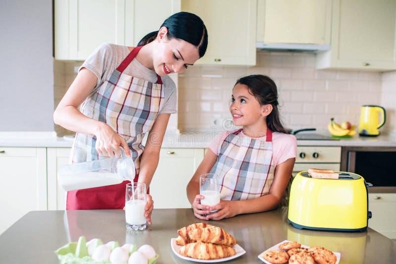 Женщина Eautiful льет в молоке к стеклянным чашкам Девушка держит ее собственную чашку и смотрит маму Она усмехается Они ожидающи стоковые изображения