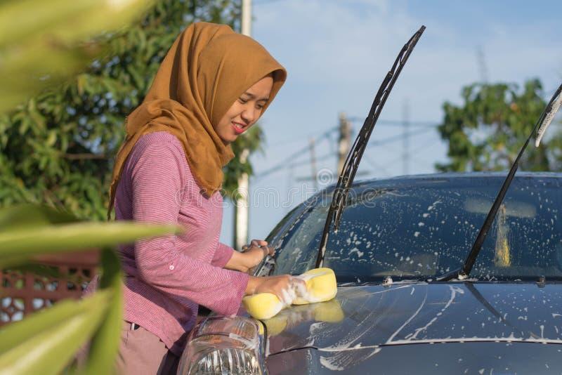 Женщина Hijab очищая ее автомобиль outdoors Обслуживание собственной личности транспорта, концепция заботы стоковое изображение rf