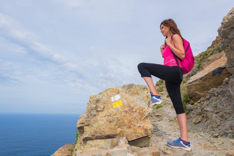 Женщина Hiker ослабленная поверх горы наслаждаясь красивым стоковые фото