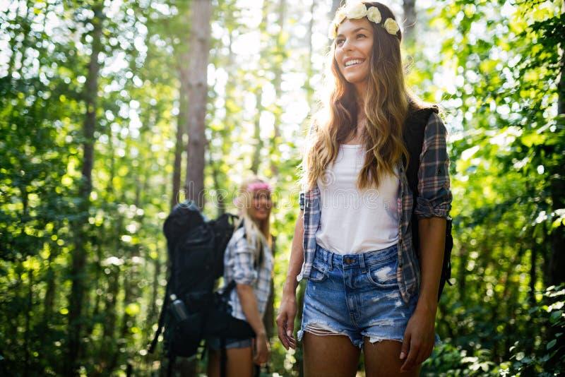 Женщина Hiker с рюкзаком идя на путь в лесе лета стоковое фото