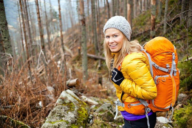 Женщина hiking в тропке леса осени стоковое фото