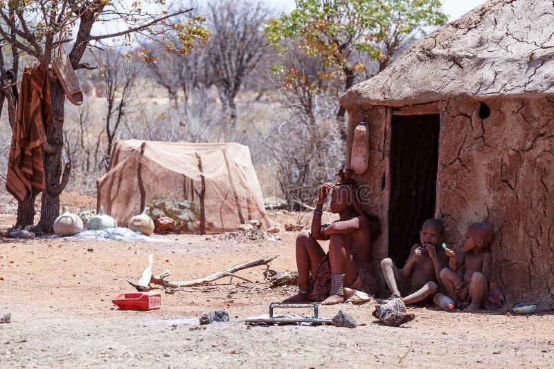 Женщина Himba с childs на шеи в деревне стоковое изображение