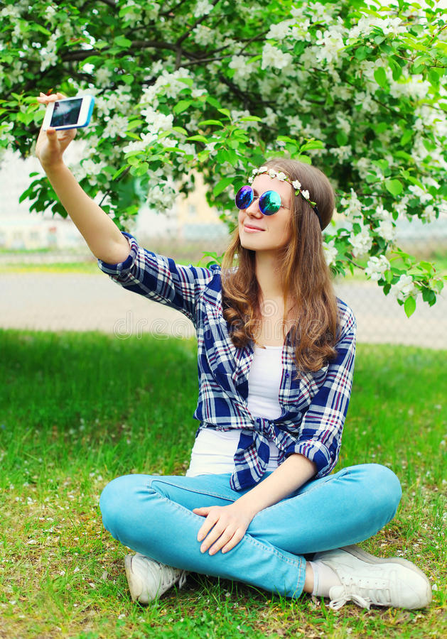 Женщина Hippie делает автопортрет на smartphone сидя на траве в цветя саде стоковые изображения rf