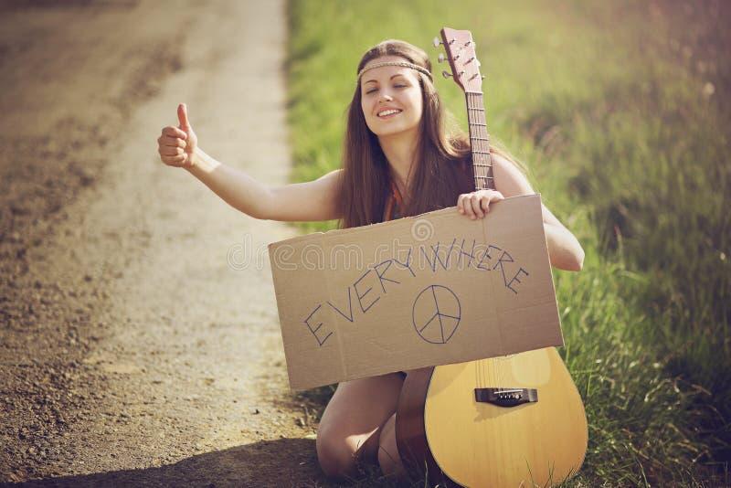 Женщина Hippie на проселочной дороге заминк-пешей стоковое фото rf