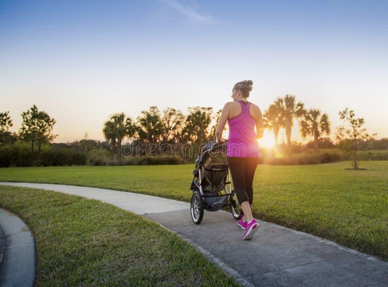 Женщина jogging и работая outdoors нажимающ ее младенца в прогулочной коляске стоковая фотография rf
