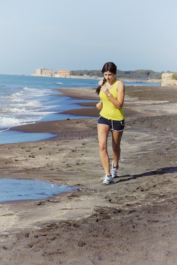 Женщина jogging на музыке пляжа слушая стоковые фото