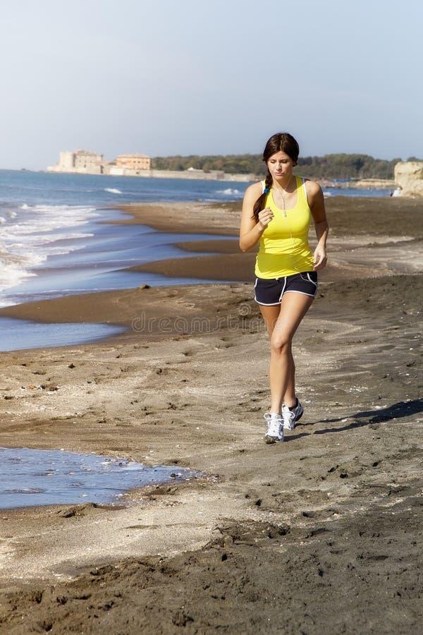 Женщина jogging на съемке музыки пляжа слушая широкой стоковое изображение rf