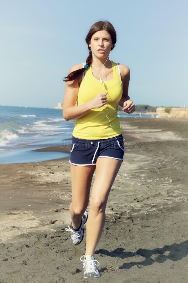 Женщина jogging на съемке средства музыки пляжа слушая стоковое изображение rf