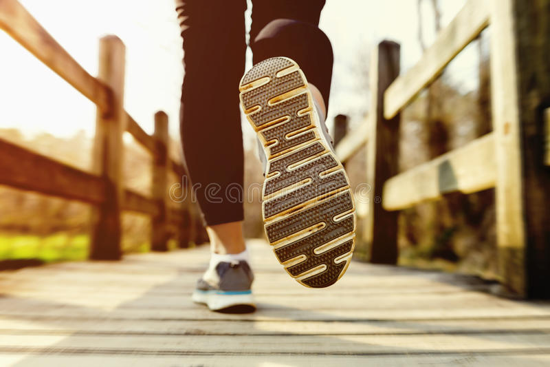 Женщина jogging через мост родины на заходе солнца стоковые фото