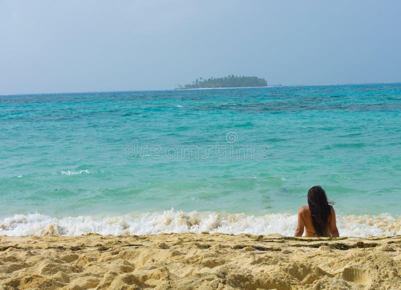 Женщина lounging на тропическом пляже стоковое фото rf