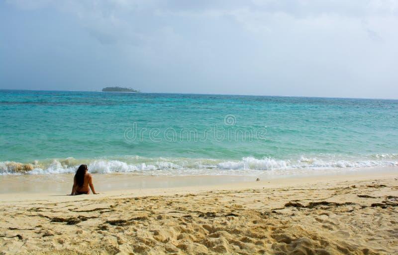 Женщина lounging на тропическом пляже стоковое фото