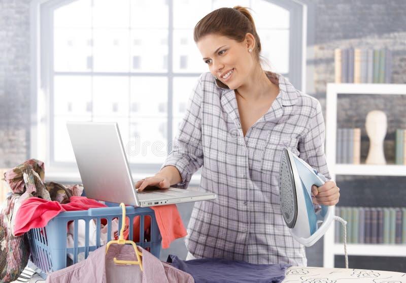 Женщина Multitasking дома стоковое фото
