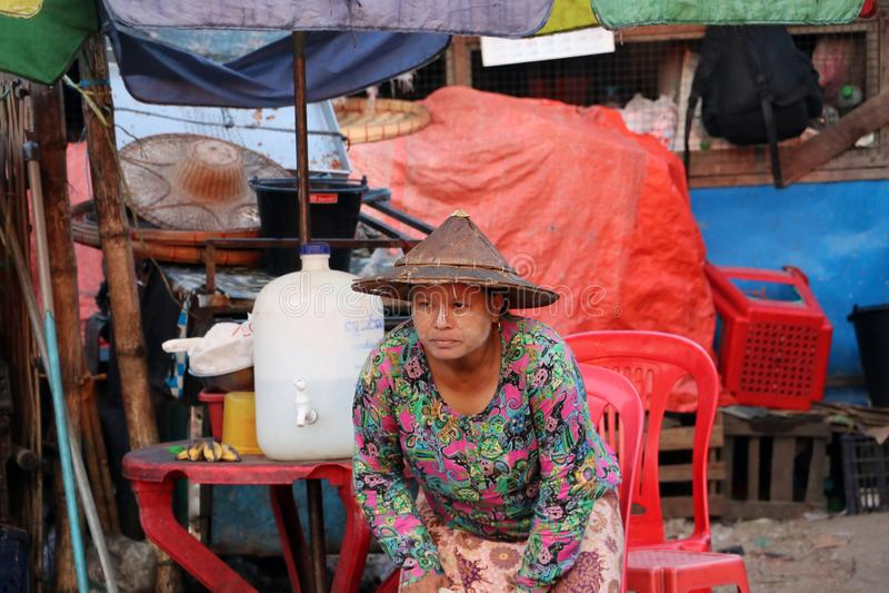Женщина Myanmese с порошком Мьянмы thanakha на ее стороне и нося конической шляпе идя сидеть в стуле стоковое фото rf