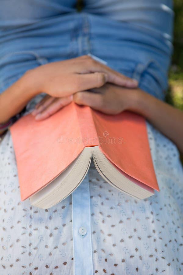 Женщина napping в парке с книгой стоковая фотография rf