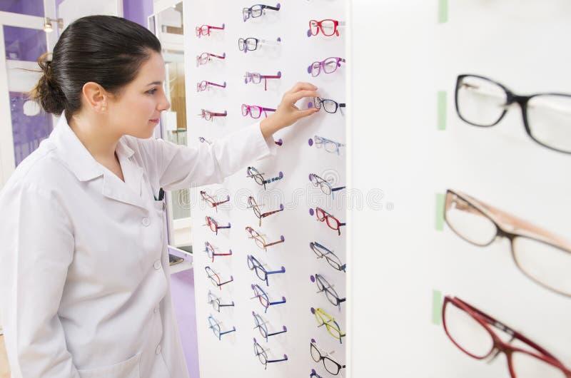 Женщина Optometrist смотря ее стекла стоковая фотография