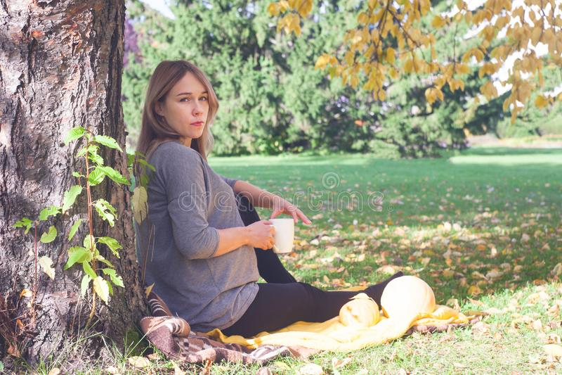 Женщина Pregrant в лесе осени на пикнике стоковое изображение