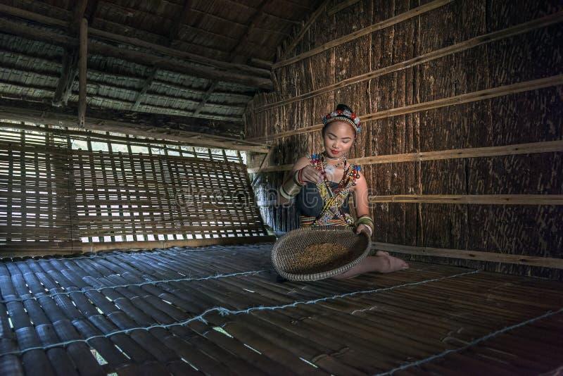Женщина Rangus племенная в ее традиционном племенном костюме работая в ее доме в Kudat, Малайзии стоковое изображение rf