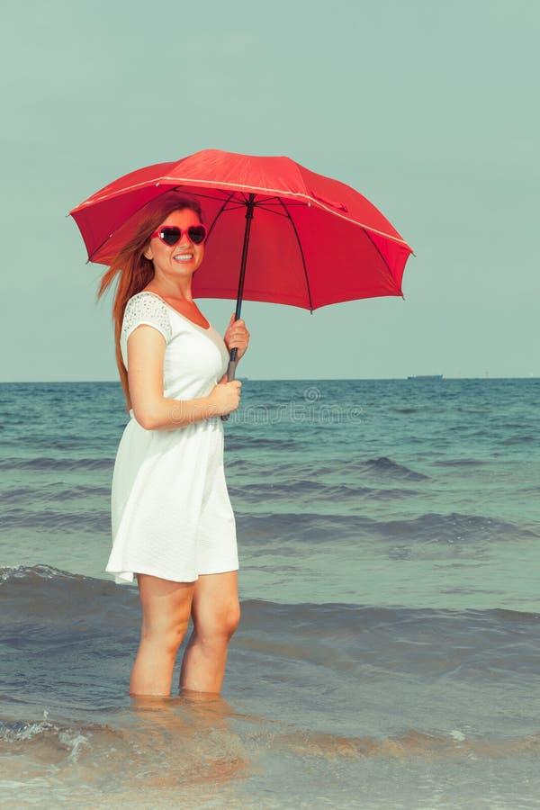 Женщина Redhead идя на зонтик удерживания пляжа стоковое изображение rf