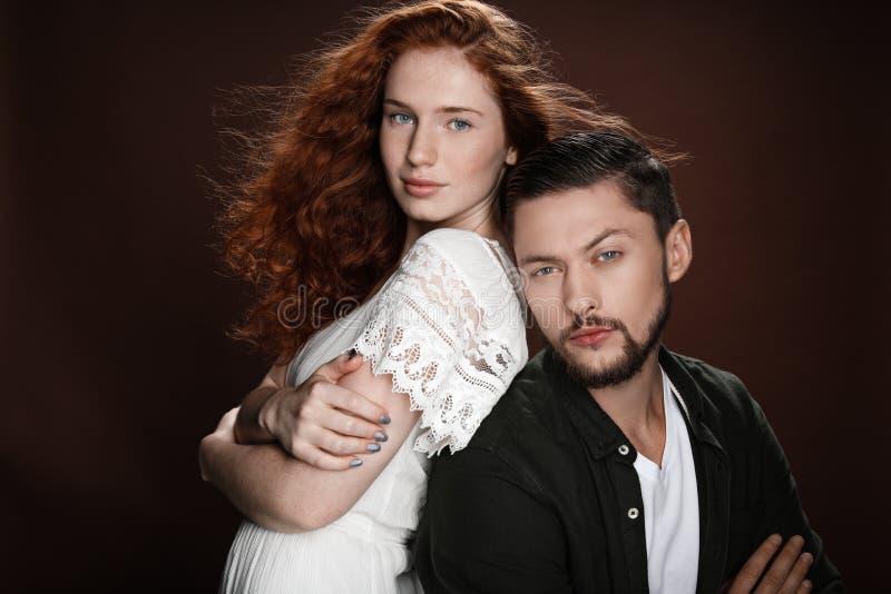 Женщина Redhead и бородатый человек стоя спина к спине пока представляющ для съемки студии стоковое фото