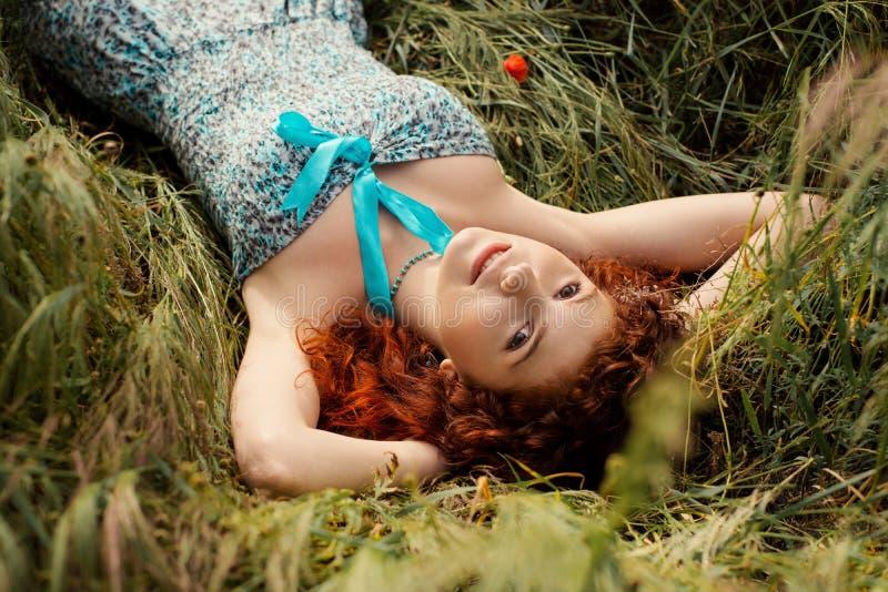 женщина redhead красивейшей травы лежа стоковое изображение