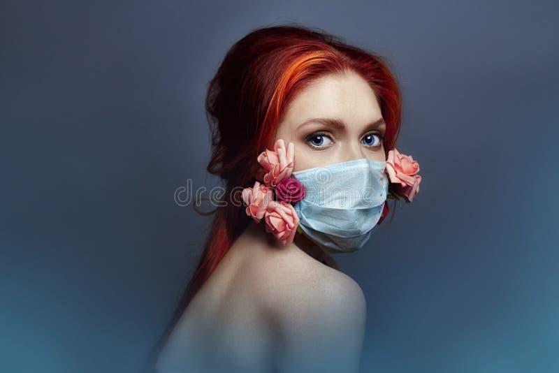 Женщина redhead моды искусства с медицинским респиратором на ее стороне, розовые цветки растет из-под маски, недостатка чистого в стоковые фото