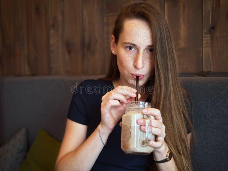 Женщина redhead портрета молодая счастливая красивая с веснушками выпивая кофе в кафе на перерыве на чашку кофе стоковые изображения rf
